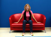 Young woman sitting on red sofa — Stok fotoğraf