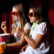 Two young girls watching in cinema — Stock Photo #7957315
