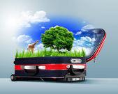 緑の自然の中で赤いスーツケース — ストック写真