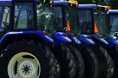 Lineup of blue tractors in a field — Stock Photo