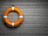 Lifebuoy on wooden wall — Stock Photo