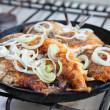 Fried fish in a frying pan - Stock Photo