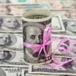 100 US dollar wrapped by ribbon on money background — Stock Photo