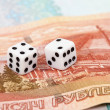 图库照片: Two dice laying over pile of money