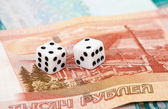 Two dice laying over a pile of money — Стоковое фото