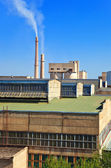 Large factory with smoking chimneys against the blue sky — Stok fotoğraf