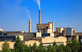 Large factory with smoking chimneys against the blue sky — 图库照片