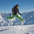 Royalty-Free Stock Photo: Woman in ski cloths jumping over the snowy mountains, austria