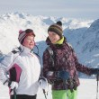 Stock Photo: Alpine skiers ( mother and daughter) mountains in the background