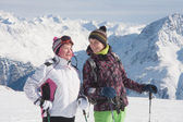 Alpine skiers ( mother and daughter) mountains in the background — Stock Photo