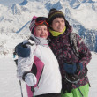 Alpine skiers ( mother and daughter) mountains in the background — Stock Photo #6966203