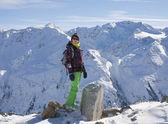 Woman in ski cloths and the snowy mountains, Austria — Stock Photo