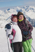 Alpine skiers ( mother and daughter) mountains in the background — Stok fotoğraf