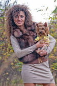 Young cheerful woman outdoors with a dog — Stock Photo