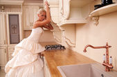 Beautiful bride stands in the kitchen — Stockfoto