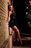 Kobieta w sukni stojącej w pobliżu ściany domu — Zdjęcie stockowe