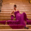 Woman in a long dress lying on the stairs — Stock Photo