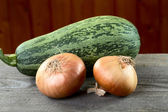 Vegetable marrow and onions on a table — Stock Photo