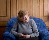 Stara kobieta siedzi na fotelu — Zdjęcie stockowe