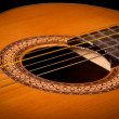 Classical guitar close up on dark - Stock Photo