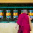 Buddhist monk rotating prayer wheels in McLeod Ganj - Stock Photo