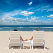 Couple in beach chairs holding hands near ocean — Stock Photo