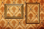 Vintage gold plated picture frames on retro wallpaper — Stock Photo