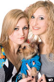 Two smiling young women with dog — Stock Photo