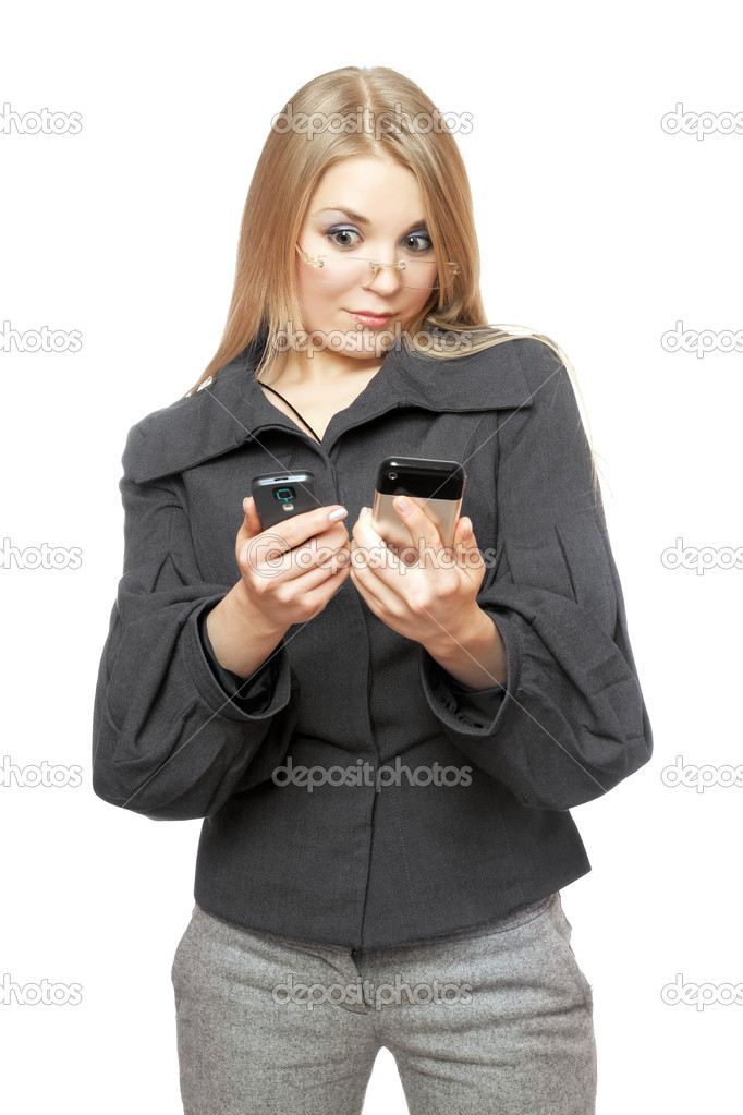 Portrait of surprised young blonde in a gray business suit with two phones — Stock Photo #6979209
