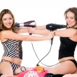 Stock Photo: Two playful girlfriends with hair dryers. Isolated