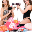 Stock Photo: Two playful young girlfriends with hair dryers