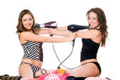 Two playful girlfriends with hair dryers. Isolated — Stock Photo