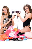 Two playful young girlfriends with hair dryers — Stock Photo