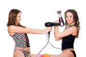 Two playful young girlfriends with hair dryers. Isolated — Stock Photo