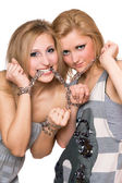 Two playful young women bound a chain — Stockfoto