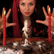 Witch at the table with candles. Isolated — Stock Photo #7575673