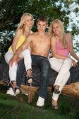 Две блондинки и молодой человек улыбается — Стоковое фото