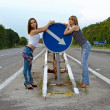 Two pretty girls stand on a road - Stockfoto