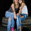 Two beautiful girls sitting on a stone - Stockfoto