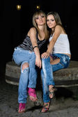 Two beautiful girls sitting on a stone — Stock Photo