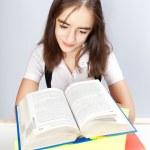 Schoolgirl reads the book — Stock Photo