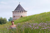 Woman in field on castle background — Stock Photo