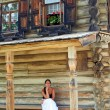 Young woman in front of Old Russian wooden house — Stock Photo