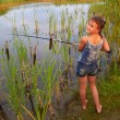 Pretty young girl fishing on river in summer — Stock Photo