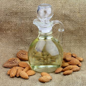 A bottle of almond oil with nuts — Stock Photo