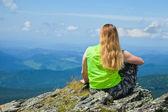 山の頂上に座っている女性 — ストック写真