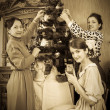 Royalty-Free Stock Photo: Retro photo of Teen girls with mother decorating Christmas tree