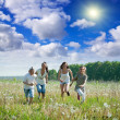 Women with teens running in grass — Stock Photo #6854239