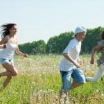 Happy women with teens running in grass — Stock Photo