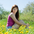 Girl sitting in dandelion meadow — Stock fotografie